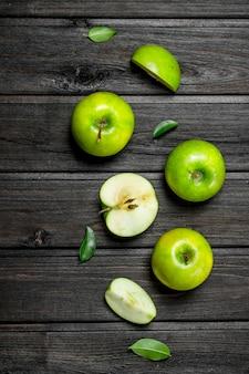 Pommes vertes et tranches de pomme. sur une table en bois sombre.