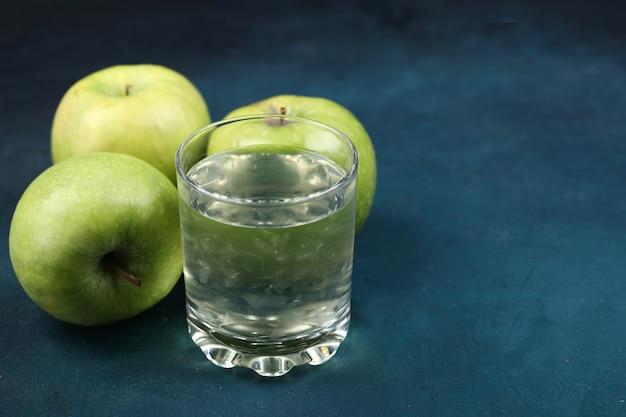 Pommes vertes avec un verre de jus de pomme.