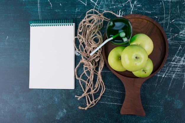 Pommes vertes avec un verre de jus sur un rustique avec un cahier de côté.