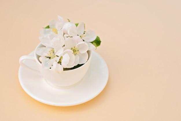 Pommier de printemps blanc fleurs en fleurs dans une tasse de café sur un fond beige. concept de printemps été. carte de voeux. copiez l'espace.