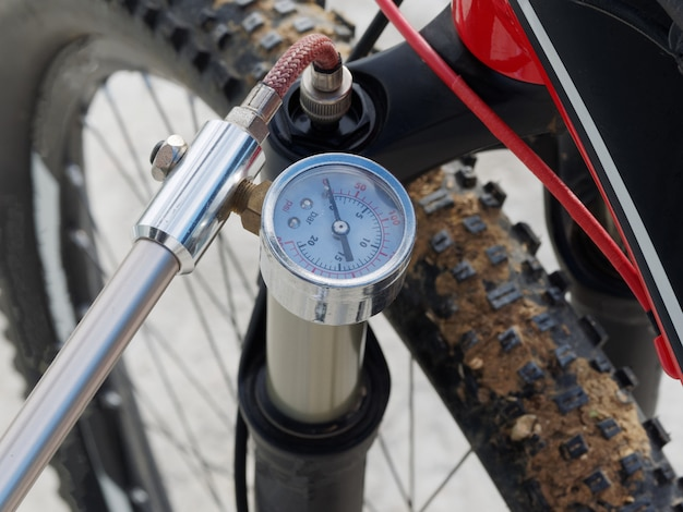 Pompage avant, amortisseur huile-air de vélo à l'aide d'une pompe à main spécialisée.