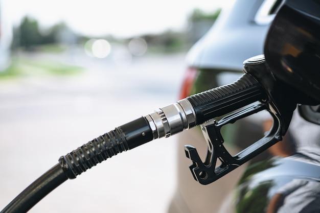 Pompage de l'essence dans une voiture brune à la station-service