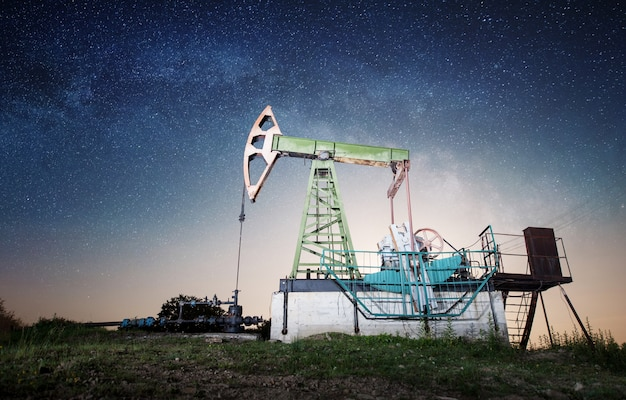 Pompe à huile sur le champ de pétrole dans la nuit