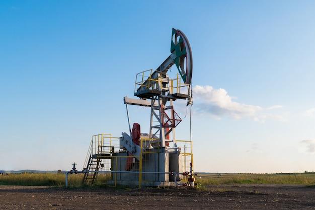 Pompe à huile de travail sur le sol parmi les champs verts