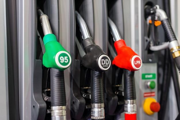 Pompes à essence colorées remplissant des buses, station d'essence dans un service dans la journée.