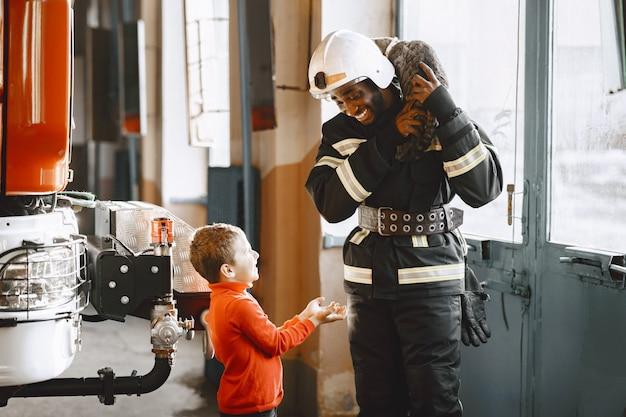 Pompier arfican en uniforme. l'homme se prépare à travailler. guy avec enfant.