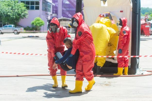 Un pompier et une combinaison de protection contre les dangers transportent la victime du sauvetage