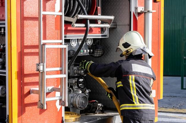 Pompier équipé manipulant une pompe d'extraction d'eau, à l'intérieur d'un camion de pompiers