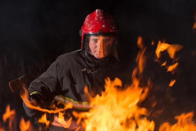 Un pompier éteint un feu la nuit