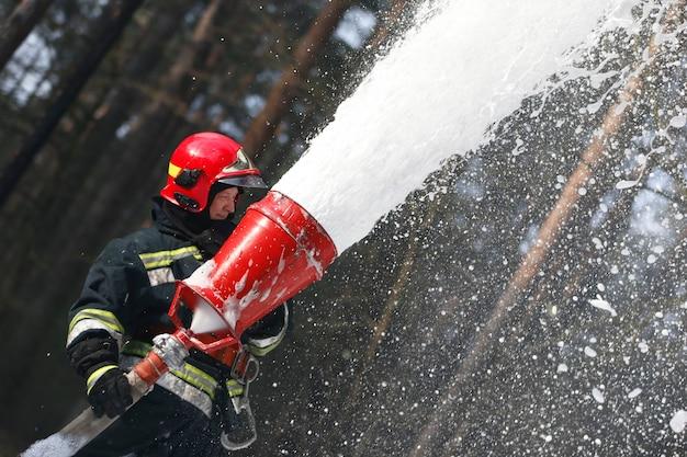 Le pompier éteint un incendie. incendie de forêt. se battre avec le feu.