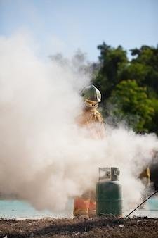 Pompier avec feu et costume pour protéger le pompier pour la formation des pompiers.