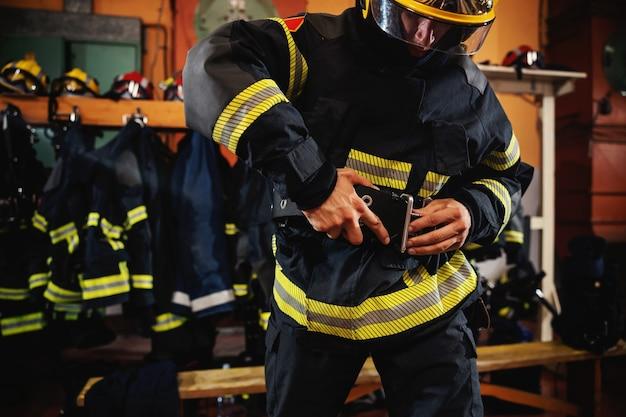 Pompier portant un uniforme de protection et se préparant à l'action en se tenant debout dans la caserne des pompiers.