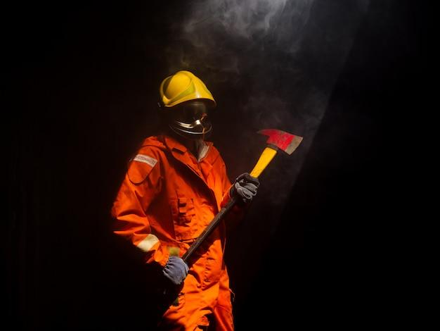 Un pompier pulvérise de l'eau pour allumer une formation au feu dans un atelier de voiture en feu