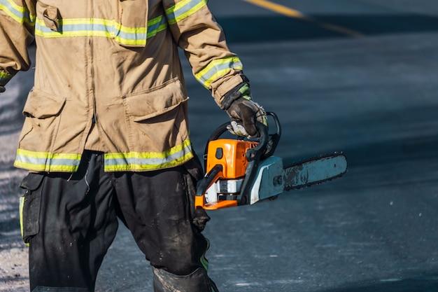 Pompier avec tronçonneuse en sauvetage.