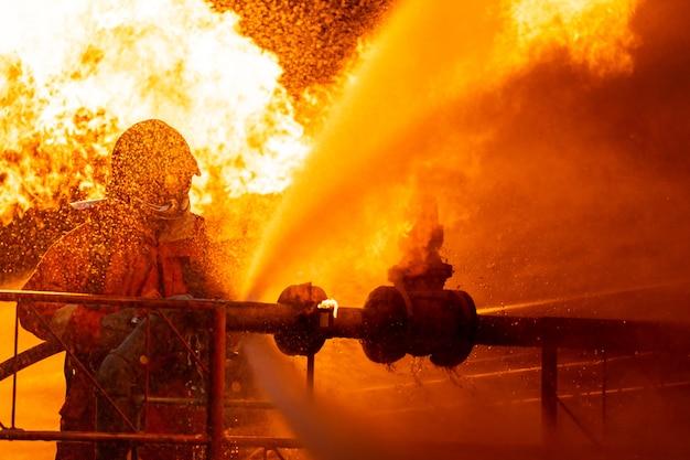 Pompier utilisant un brouillard d'eau pour lutter contre la flamme du feu provenant d'une fuite d'oléoduc