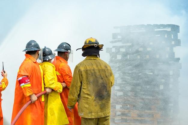 Pompier utilisant l'eau et l'extincteur à la lutte contre la flamme du feu