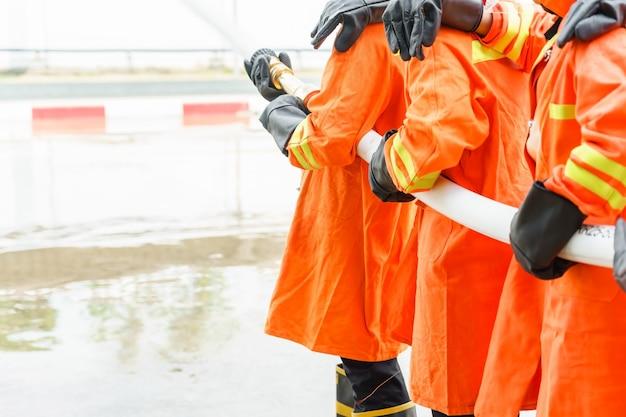 Pompier utilisant un extincteur et de l'eau d'un tuyau pour lutter contre l'incendie