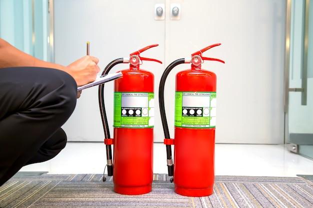 Pompier vérifiant le niveau de la jauge de pression de l'extincteur.
