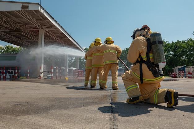 Pompiers en formation avec tuyau d'arrosage