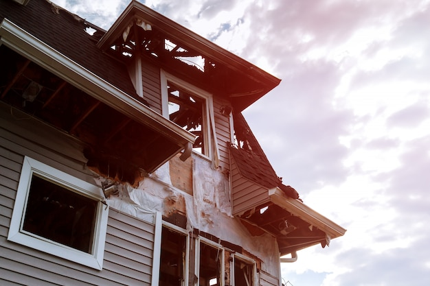 Les pompiers secouristes éteignent un incendie sur le toit. le bâtiment après l'incendie. fenêtre brûlée. maison en ruine. catastrophe.