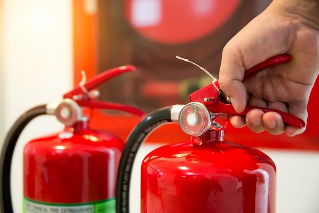 Les pompiers vérifient la poignée du réservoir des extincteurs dans le bâtiment