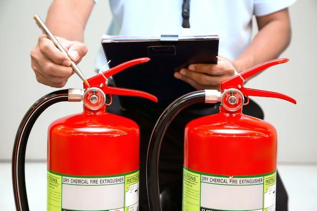 Les pompiers vérifient le réservoir des extincteurs dans le bâtiment.
