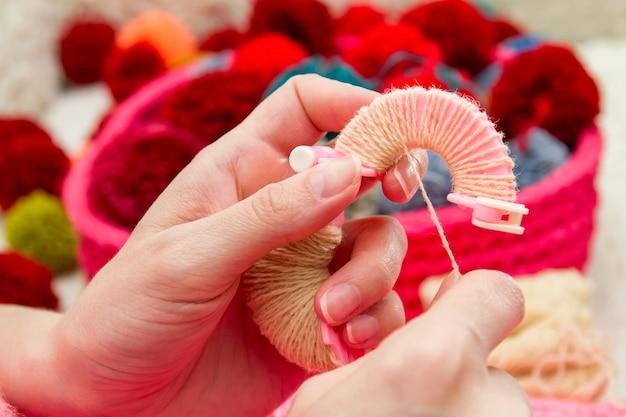 Pompons faits à la main. le processus de fabrication de pompons à partir de fils par une femme