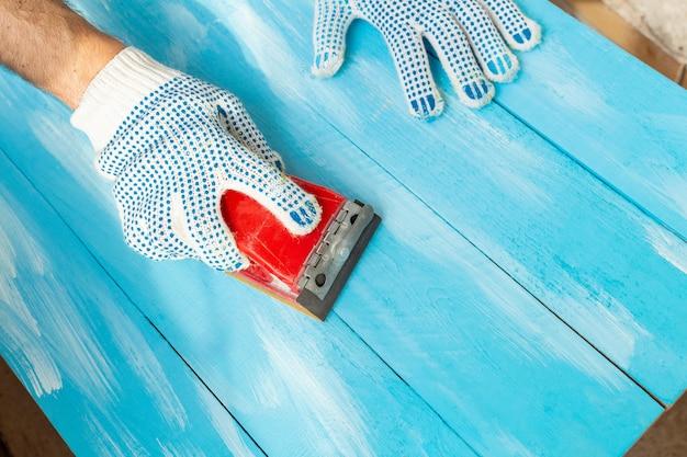 Ponçage avec des abrasifs dans une main éponges de ponçage peint fond de table en bois bleu close up