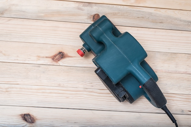 Ponceuse à bande électrique, ponceuse posée sur une table en bois marron clair. directement au-dessus, copiez l'espace.