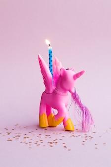Poney rose mignon avec une bougie d'anniversaire