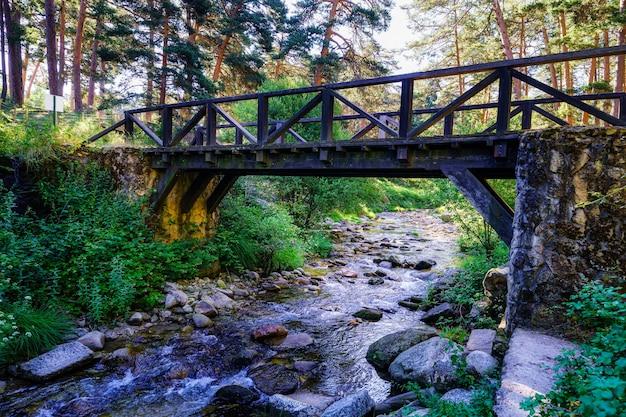 Pont de bois au-dessus du ruisseau forestier au lever du soleil. navacerrada.