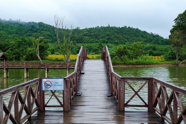Un pont en bois au milieu du marais avec un panneau interdisant de nourrir les poissons