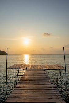 Pont en bois dans la mer et reflets dorés du soleil