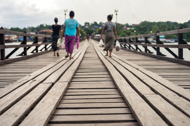 Pont en bois avec des gens flous mon marchant à travers la rivière songkalia à viilage, sangkhlaburi, kanchanaburi, thaïlande. célèbre destination de voyage ou vacancier au siam.