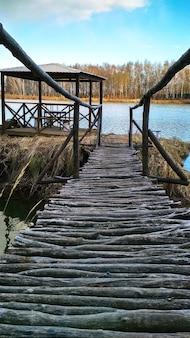 Pont en bois mène à un belvédère sur la rive du lac