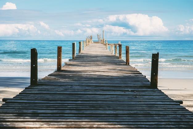 Pont en bois sur la plage avec ciel.
