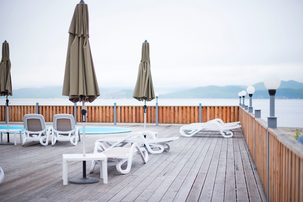 Pont en bois plage mer océan resort soleil chaise longue parasol hôtel piscine ciel lever du soleil.