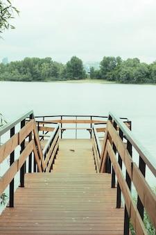 Le pont en bois avec une plate-forme d'observation et des bancs sur le lac.