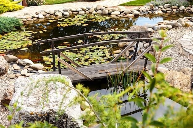 Pont en bois rétro sur l'étang avec des nénuphars dans le parc de la ville.