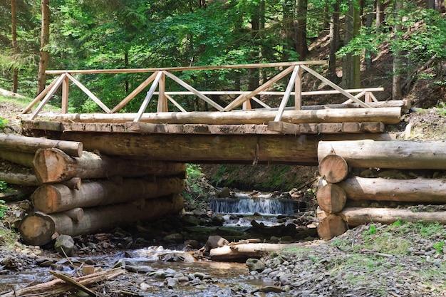 Un pont en bois à travers un ruisseau de montagne en forêt