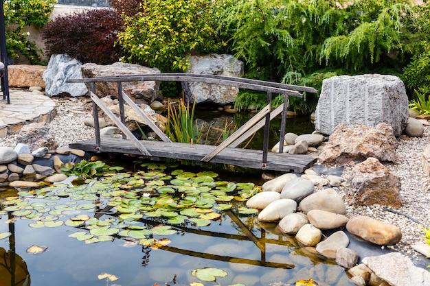 Pont en bois vintage sur l'étang avec des nénuphars dans le parc de la ville.