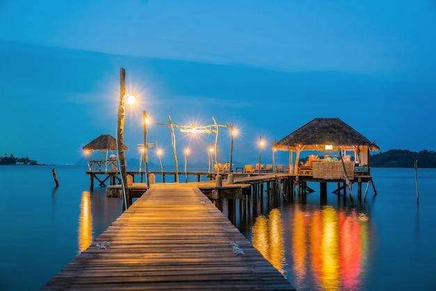Pont boisé vers le port de koh mak après le coucher du soleil