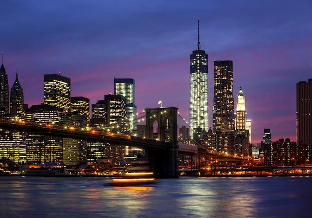 Pont de brooklyn, east river et manhattan la nuit avec lumières et reflets. la ville de new york