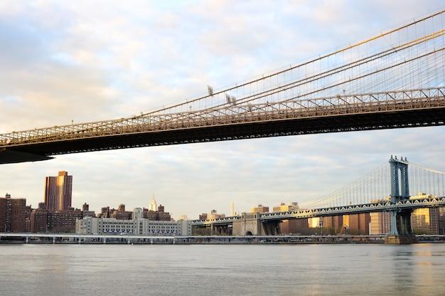 Pont de brooklyn de new york city avec les toits du centre-ville sur east river au coucher du soleil