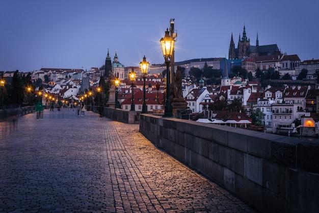 Pont charles avec statues lanternes et château de prague en arrière-plan tôt le matin