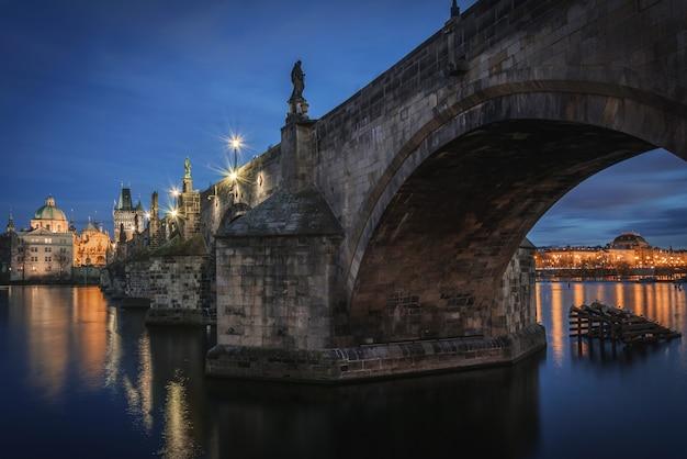 Pont charles sur vltava avec théâtre national sous l'arche de nuit à prague