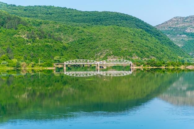 Le pont de chemin de fer passe sur une rivière de montagne.