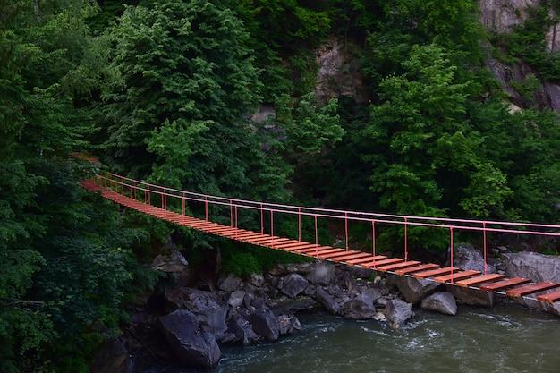 Pont de corde suspendu sans personnes avec des rives rocheuses au-dessus d'une rivière de montagne sur fond de montagne dans une végétation verte luxuriante