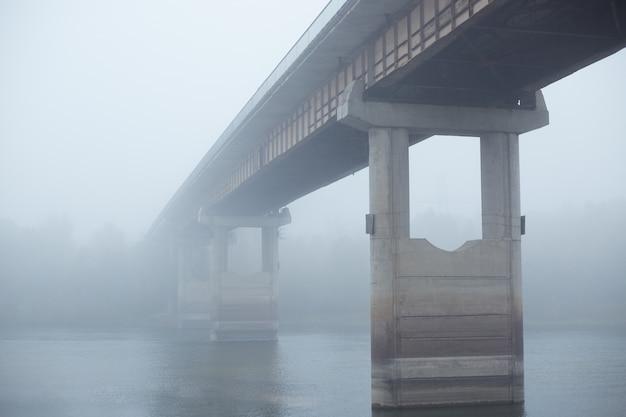 Pont dans le brouillard, pont en béton à travers la rivière