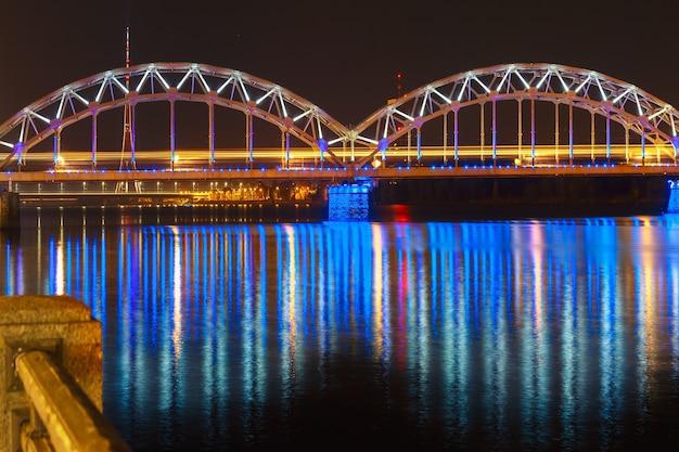 Pont ferroviaire illuminé et rivière daugava, lettonie